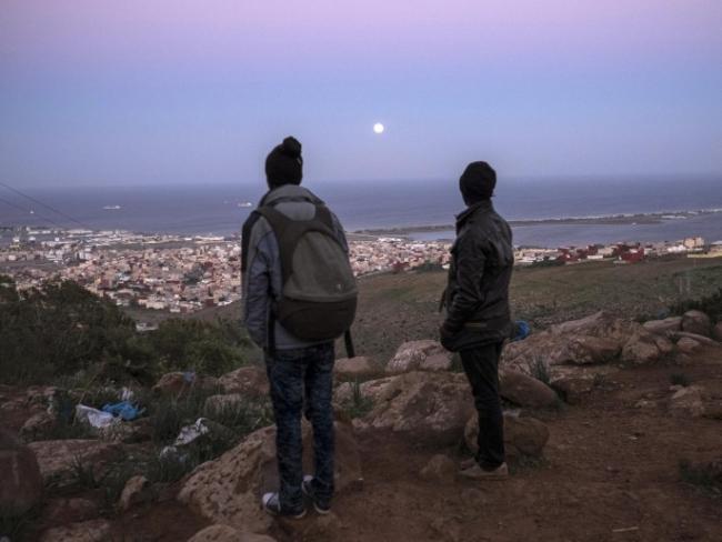 Dos inmigrantes africanos mirando a Al-Nazur, la última ciudad de camino a Europa.  Foto: AP