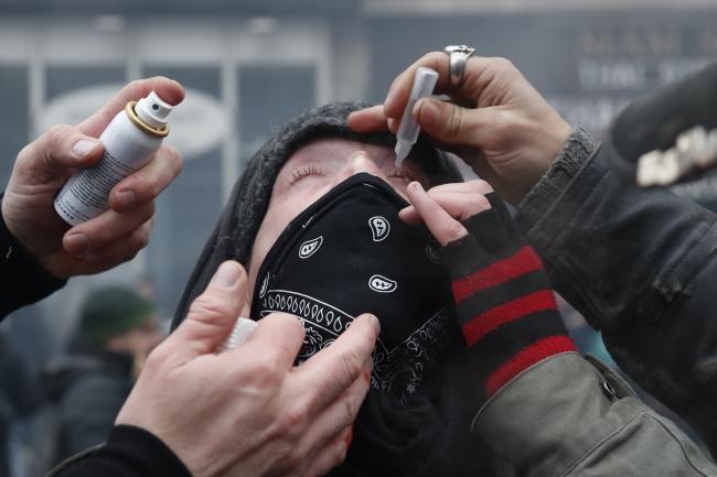 Polisin kullandığı gazlara karşı koruyucu göz damlası kullanan bir gösterici. 5 Aralık 2019, Paris | Fotoğraf: AFP