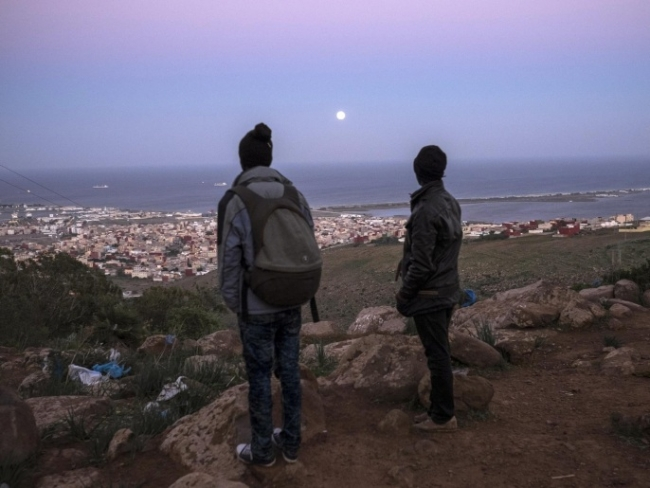 Avrupa'ya geçişteki son kent Al-Nazur'a bakan iki Afrikalı göçmen. Fotoğraf: AP