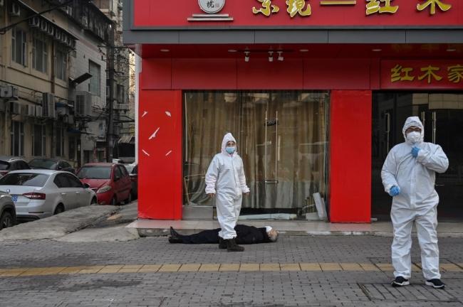 Koronavirüs sebebiyle hayatını kaybeden bir Wuhanlı yerde yatıyor. | Fotoğraf: AFP