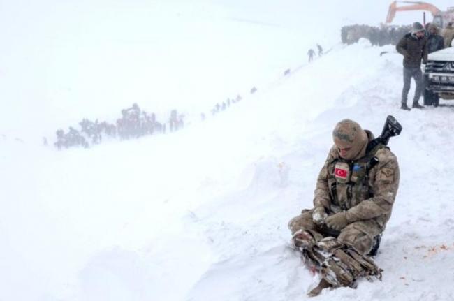 Van'daki çığın altında kalan arkadaşlarına bakan askerin fotoğrafı. Foto: AA