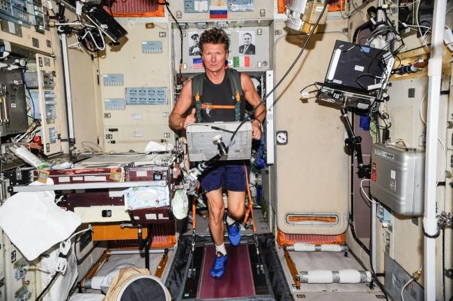 Uzay aracı içinde spor yapan bir astronot.